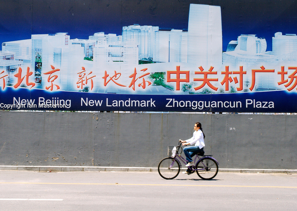 Woman cycles past large billboard advertising new high technology property development in Zhongguncun district of Beijing China