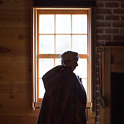 Eve Allen, a docent at The Museum of the Waxhaws, opens a window inside the Secrest Homestead.