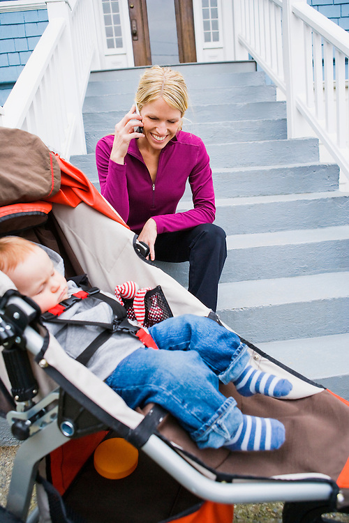 Mother talking on cell phone while her baby sleeps in a running stroller.