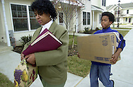 Lois Hinson, left, and her son Damier Belgrave, 11, center, carry belongings, along with cousin Mikaun Wiggins, 10, right, as they move into their new home in Chatham Estates, Saturday, March 16 2002, in Chester, Pa. Chatham Estates was built through the U.S. Department of Housing and Urban Development's HOPE VI program, which called for demolishing decrepit public-housing towers and replacing them with townhouses and houses.  (Photo by William Thomas Cain/photodx.com)