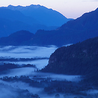 Canada, British Columbia, Squamish, Sunrise over mist-filled Squamish River valley with Coast Range mountains in distance