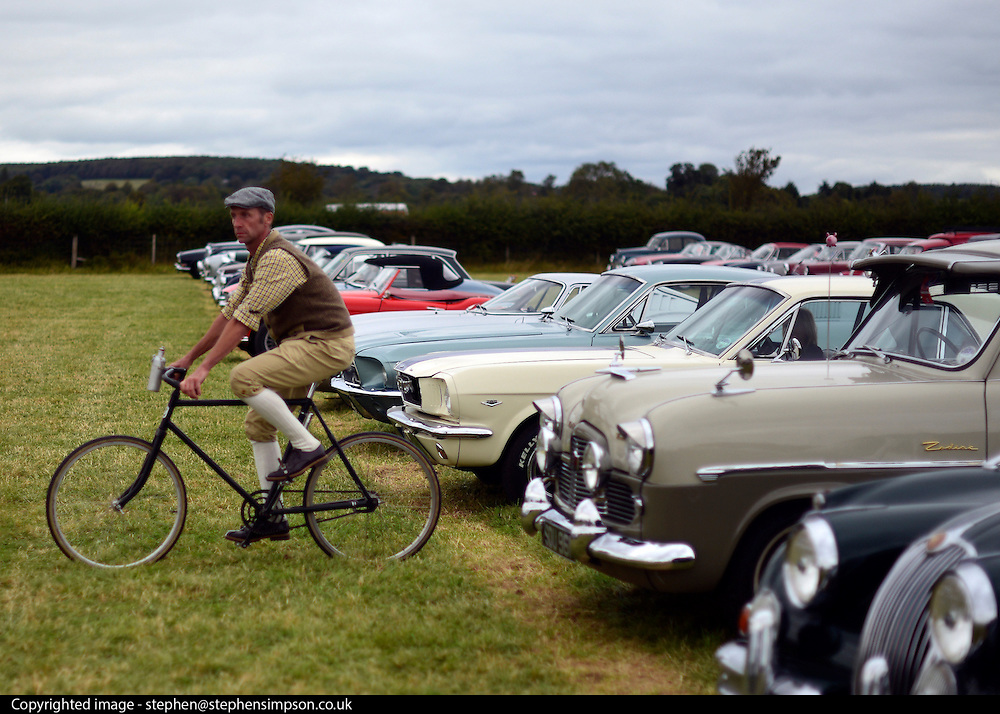 © Licensed to London News Pictures. 16/09/2012. Goodwood, UK . A man rides a bicycle through the cars in the car park. People enjoy the atmosphere at the 2012 Goodwood Revival. The event recreates the glorious days of motor racing and participants are encouraged to dress in period dress. Photo credit : Stephen Simpson/LNP