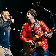 Micahel Franti and Spearhead perform to a packed crowd in Teton Village, Wyoming. Michael Franti and spectator sing song together on stage.