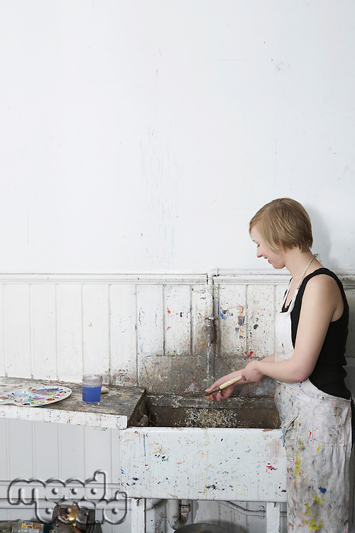 Artist cleaning paintbrush at sink in studio side view