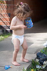 Little girl playing with a tin can in the garden,