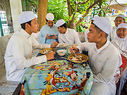10 APRIL 2015 - BANGKOK, THAILAND: Thai Muslim teenagers eat lunch at a food stall in a Muslim neighborhood near Ton Son Mosque in Bangkok. A Pew Research Center study recently released identified Islam as the fastest growing religion in the world. Masjid Ton Son was the first mosque in Bangkok, founded in 1688 during the reign of King Narai, of the Ayutthaya era. Muslims are about 5 percent of Thailand, but make up a bigger proportion of Bangkok. Thailand's deep south provinces are Muslim majority.    PHOTO BY JACK KURTZ