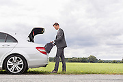 Full length side view of young businessman unloading luggage from broken down car at countryside