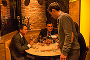 New York, NY, Sept. 30, 2013. Grant Reynolds, wine director at Charlie Bird, serving wine to patrons. (L to R) Michael Liou and Juan Ruiz.