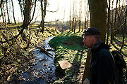Terry, activist from Cork, standing beside a stream that now runs under the partly built M3 motorway that is controversially cutting through the national monument of Rath Lugh, an ancient promontory fort that was a defensive position for the Hill of Tara, the sea of the High Kings of Ireland. Behind Terry is a large mound of construction rubble. The trees in the photograph will be cleared by the motorway construction. ..