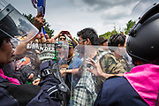 07 AUGUST 2013 - BANGKOK, THAILAND: Thai riot police and anti-government protesters confront each other at Ratchawithi intersection in Bangkok. About 2,500 protestors opposed to an amnesty bill proposed by Thailand's ruling party marched towards the Thai parliament in the morning. The amnesty could allow exiled fugitive former Prime Minister Thaksin Shinawatra to return to Thailand. Thaksin's supporters are in favor of the bill but Thai Yellow Shirts and government opponents are against the bill. Thai police deployed about more than 10,000 riot police and closed roads around the parliament. Although protest leaders called off the protest rather than confront police, a few people were arrested for assaulting police when they tried to break through police lines. Several police officers left the scene under medical care after they collapsed in the heat.    PHOTO BY JACK KURTZ