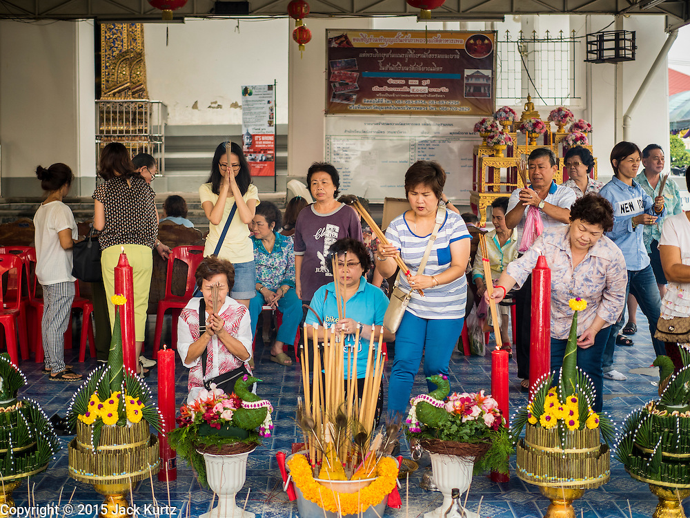 11 SEPTEMBER 2015 - BANGKOK, THAILAND:  People who donated food to Wat Kalayanamit pray before a food distribution for poor members of the community at Wat Kalayanamit in the Thonburi section of Bangkok. Food distribution is a common way of making merit in Chinese Buddhist temples. Wat Kalayanamit, a Thai Theravada temple, was founded by a Chinese-Thai family in the 1820s and observes both Thai and Chinese Buddhist traditions. The food distribution was not related to the temple's efforts to evict people living on the temple grounds, but many of the people at the food distribution live in the houses the temple plans to raze.   PHOTO BY JACK KURTZ
