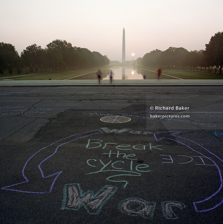During a journey into America's hinterlands, days after the September 11th attacks in New York and Washington DC, we see anti-war graffiti written in a circular chalk graphic on the path in front of the Lincoln Memorial of Washington DC's National Mall. The words 'Break the Cycle (of) War' appear as early morning joggers blur in the background beyond whom, the Washington Memorial is seen below the rising sun and a rising mist. Soon afterwards the graffiti was hosed away by park rangers, eager to remove anti-militarist and unpatriotic sentiments at a time before the military was about to mobilise once again with many American lives lost. In outpourings of grief, anger and patriotic rhetoric, flags were flown as never before as America sought to express their emotions and unity..