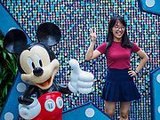 "12 DECEMBER 2018 - SINGAPORE:  A woman poses for a picture with Minnie Mouse at a Christmas display on Orchard Road. Orchard Road is the main shopping district of Singapore and for years hosts a large light display around Christmas. The main sponsor of this year's display is the Disney Company and the displays are decorated with characters from the Disney entertainment universe. This has upset some religious leaders in Singapore and the National Council of Churches of Singapore (NCCS) sent a letter to the Singapore Tourism Board (STB) expressing its concern about the ""increasing secularisation and commercialization of Christmas"" in Singapore. The STB reached out to the NCCS, but the Orchard Road lights will remain on through the holidays.   PHOTO BY JACK KURTZ"