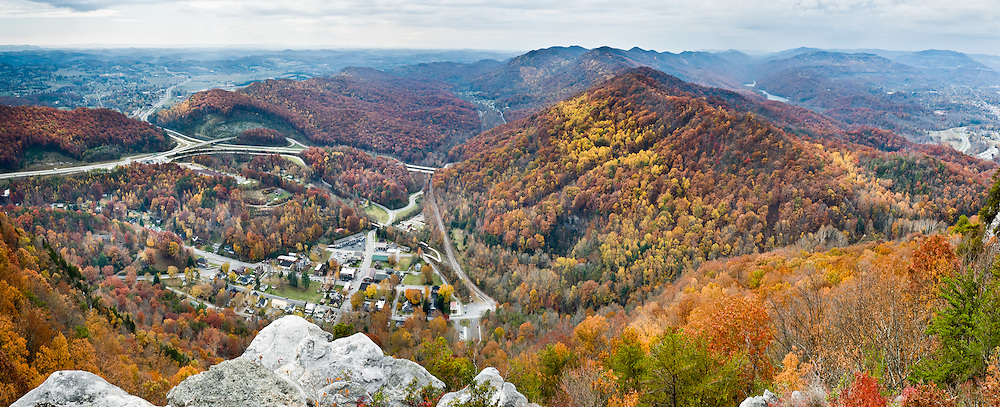 Pinnacle Overlook (2440 feet elevation) in Virginia, in Cumberland Gap National Historic Park, rises 1400 feet above the town of Cumberland Gap, Tennessee. Tristate Peak rises to 1990 feet elevation on the middle right, where the states of Kentucky, Tennessee, and Virginia meet, as resolved in 1803. On the far right is the pass of Cumberland Gap (elevation 1600 feet / 488 meters) in the Cumberland Mountains region of the Appalachian Mountains, also known as the Cumberland Water Gap, famous in American history for its role as the chief passageway through the central Appalachians and as an important part of the Wilderness Road. Long used by Native Americans, the path was widened by a team of loggers led by Daniel Boone, making it accessible to pioneers, who used it to journey into the western frontiers of Kentucky and Tennessee. The gap was formed by an ancient creek, flowing southward, which cut through the land being pushed up to form the mountains. As the land rose even more, the creek reversed direction flowing into the Cumberland River to the north. Panorama stitched from 3 overlapping photos.