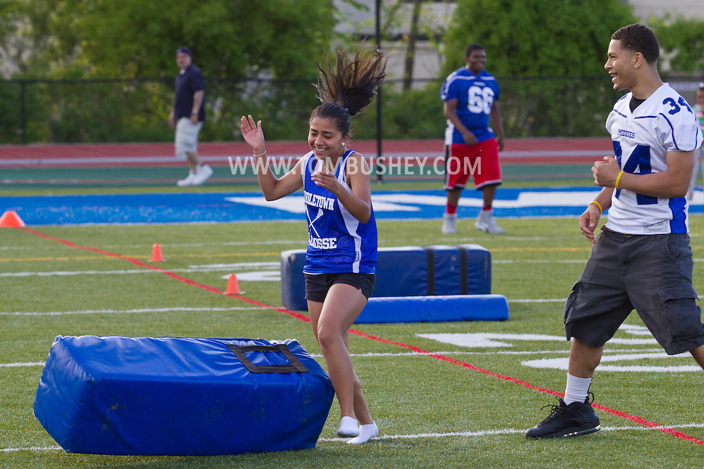 Middletown, New York - A girl laughs after knocking over a cushion held by a Middletown High School football player during a drill at Faller Stadium during Family Fun Night on May 17, 2013.