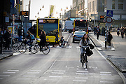 In Utrecht fietst een vrouw over de busbaan, waar ook een taxi rijdt en bussen van Qbuzz. Ander verkeer steekt over.<br /> <br /> In Utrecht a woman cycles on the bus lane, where cabs and busses ride and other traffic is crossing.