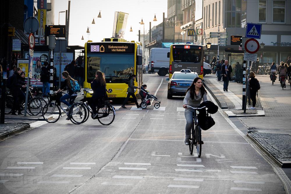 In Utrecht fietst een vrouw over de busbaan, waar ook een taxi rijdt en bussen van Qbuzz. Ander verkeer steekt over.<br /> <br /> In Utrecht a woman cycles on the bus lane, where cabs and busses ride and other traffic is crossing.