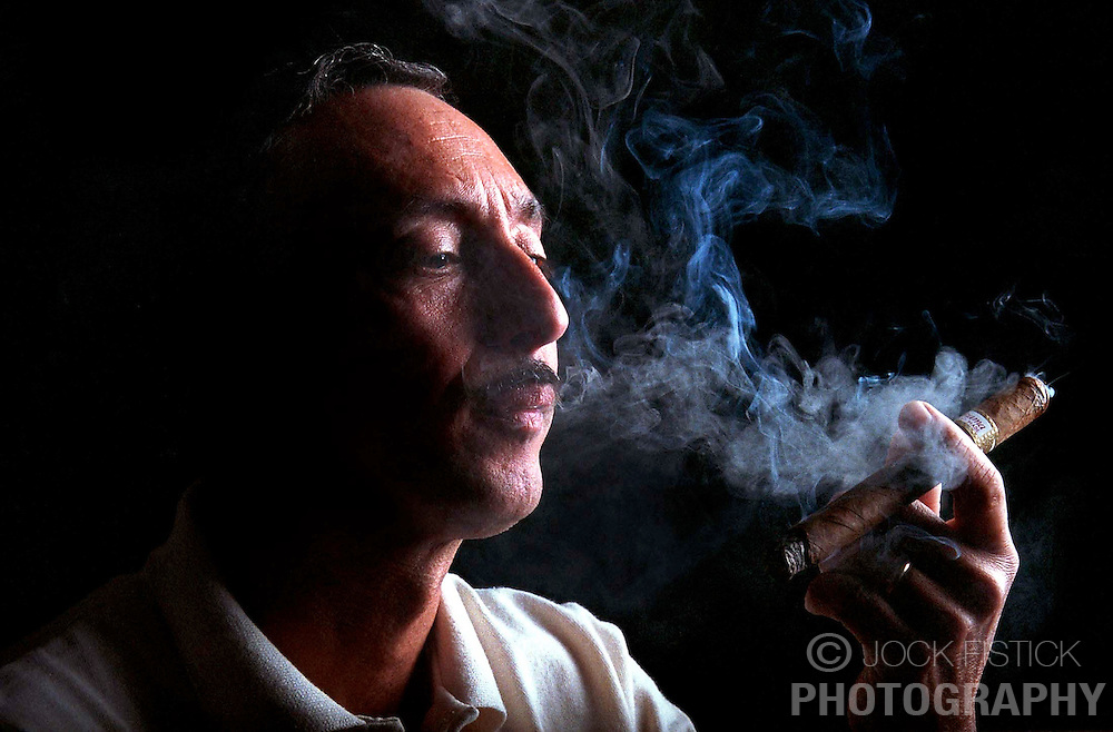 Wallace Reyes owner of the Gonzales Habano Cigar Co., taste tests one of his hand-made cigars.