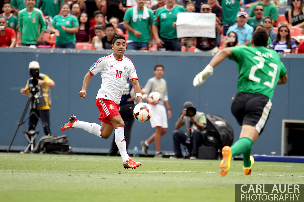 July 14 2013:  Mexico Forward Marco Fabian (10) brings the ball towards the rushing Martinique Goalie Kevin Olimpa (23) during the first half of the CONCACAF Gold Cup soccer match between Martinique and Mexico at Sports Authority Field in Denver, CO. USA.