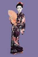 Portrait of Japanese woman in kimono holding folding fan against purple background