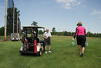 Phillip Roy gets out his club while his daughter Dale Nims gets them each a bucket of balls to warmup on the practice green at Lochmere Golf and Country Club on Monday morning.  (Karen Bobotas/for the Laconia Daily Sun)