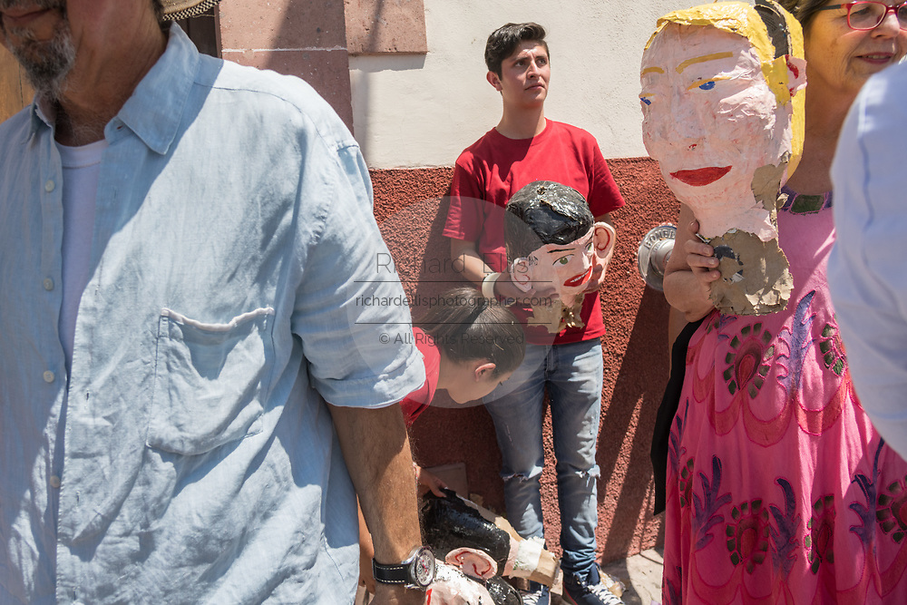 People walk away with the head of an effigy of U.S. President Donald Trump after it was exploded during the Burning of Judas Easter-time ritual marking the end of Holy Week April 1, 2018 in San Miguel de Allende, Mexico. While the tradition includes burning a paper effigy of Judas a recent popular addition has been paper doll caricatures of Donald Trump across Mexico.