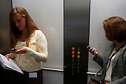 Two ladies simultaneously check mobile phone messages in a lift at an auditing company's London headquarters