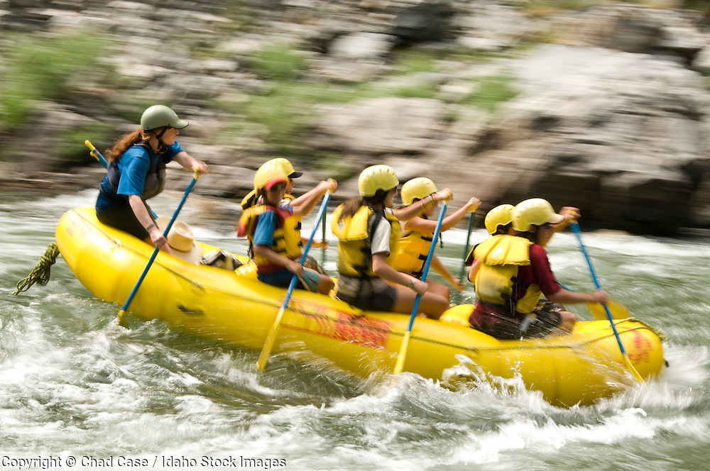 Idaho. Middle Fork Salmon River. Motion blur of people paddling through white water while on rafting trip. MR