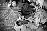 One day after the delivery, Hamida has returned back to the camp and breastfeeds her baby in their tent. Karachi, Pakistan, 2010