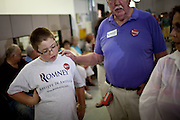 Christopher Handwerger, 11, left, waits with his grandfather, right, for GOP presidential candidate Gov. Mitt Romney to speak at a campaign rally at EIT LLC, and electronics design and manufacturing company, in Sterling, Virginia, June 27, 2012.