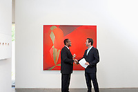 Two people shaking hands in front of wall painting