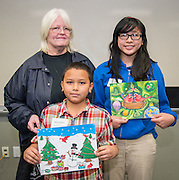 Park Place Elementary School art teacher Kathleen McAuliffe poses with Adrian Pizarro and DeBakey High School student Tam Ngo with their winning designs during the Houston ISD official holiday card reception, November 8, 2013. Ngo is a former student of McAuliffe.