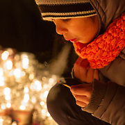 Steam comes out of a young boy's mouth as he blows out a match after lighting candles. The Feast Our Lady of Guadalupe celebration annual two-day feast celebration of Mexico's patron saint. Braving extremely cold weather, believers from the Chicago area and other parts of the United States gather day and night to pay homage at the shrine.   Photography by Jose More