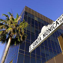 Photo of Santa Monica Blvd street sign with a palm tree and office building in Beverly Hills California. Beverly Hills is a wealthy community of the rich and famous in Los Angeles County in Southern California.