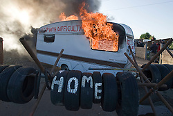 © Licensed to London News Pictures. 19/10/2011. Crays Hill, UK. A burning caravan inside Dale Farm Travellers site today (19/10/2011). Residents at Dale Farm, the UK's largest illegal traveller site being evicted today (19/10/2011) following a long dispute with Basildon Council . Travellers and activist had barricaded themselves in to the site in an attempt to prevent their eviction. Photo credit: Ben Cawthra/LNP