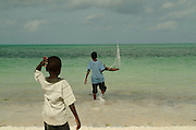 Young boys with their model boat made from palm leaves try it out on the shores of Zanzibar. Jambiani beach, Zanzibar, Eastern Africa.