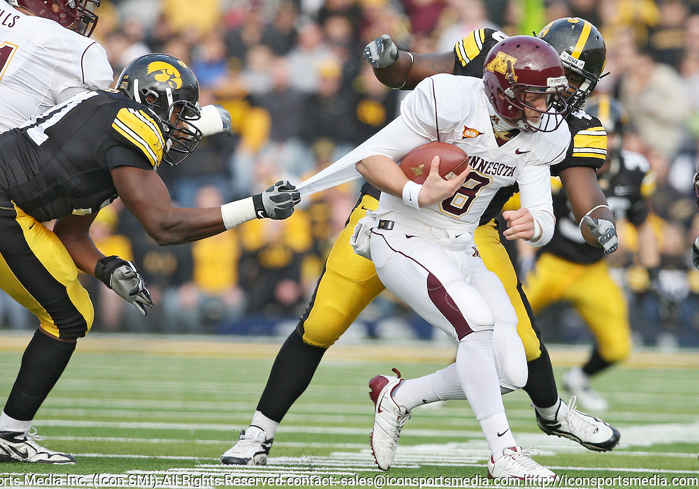 November 21, 2009: Minnesota quarterback Adam Weber (8) is pulled down by Iowa defensive tackle Broderick Binns (91) as Iowa defensive tackle Christian Ballard (46) closes in during the first half of the Iowa Hawkeyes 12-0 win over the Minnesota Golden Gophers at Kinnick Stadium in Iowa City, Iowa on November 21, 2009.