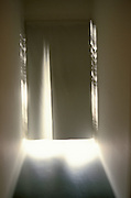 Abstract view of hall with light coming from under curtain