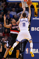 Feb 15, 2012; Oakland, CA, USA; Golden State Warriors guard Klay Thompson (11) shoots past Portland Trail Blazers small forward Nicolas Batum (88) during the second quarter at Oracle Arena. Mandatory Credit: Jason O. Watson-US PRESSWIRE