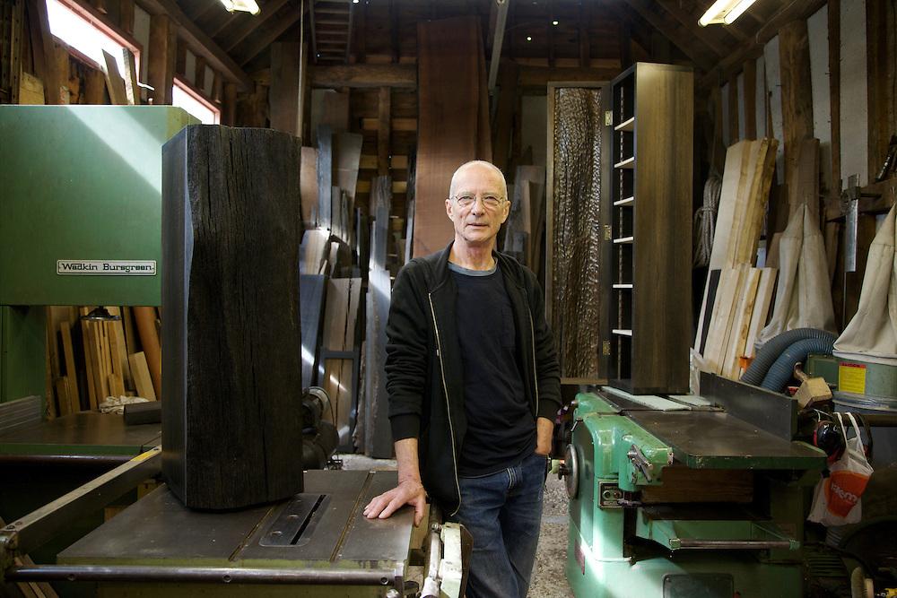 Furniture maker Adrian Swintead describing work on 2 pieces (wooden cabinets in foreground and background) displayed in his Maulden Woods studio, Bedfordshire<br /> CREDIT: Vanessa Berberian for The Wall Street Journal<br /> GURU-SWINSTEAD