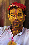 Portrait of a temple priest. Devotees gather at the Krishna Temple of Shriji, during Lathmar Holi. Men from Barsana raid the town whilst being assaulted with coloured water sprayed from rooftops, they are beaten by Nandgaon's women with large sticks and smeared with Holi coloured powders in a counterpart festival to the one held in Barsana on the previous day. The spectacle is a riot of colour amidst frenzied celebrations.