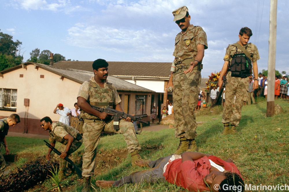 KwaZulu Natal. South Africa. 1994. Riot police over a man killed in IFP ANC clashes, KwaMashu,  KwaZulu Natal 1994.
