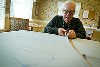 Jim Williams cuts fabric to make clothing covers Wednesday at the Four Seasons Assisted Living Community in Coeur d'Alene. Residents, staff and other volunteers in the community are crafting 100 of the items to donate to various local care facilities and KMC.