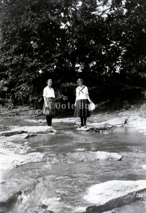 two girls standing by stream 1920s USA