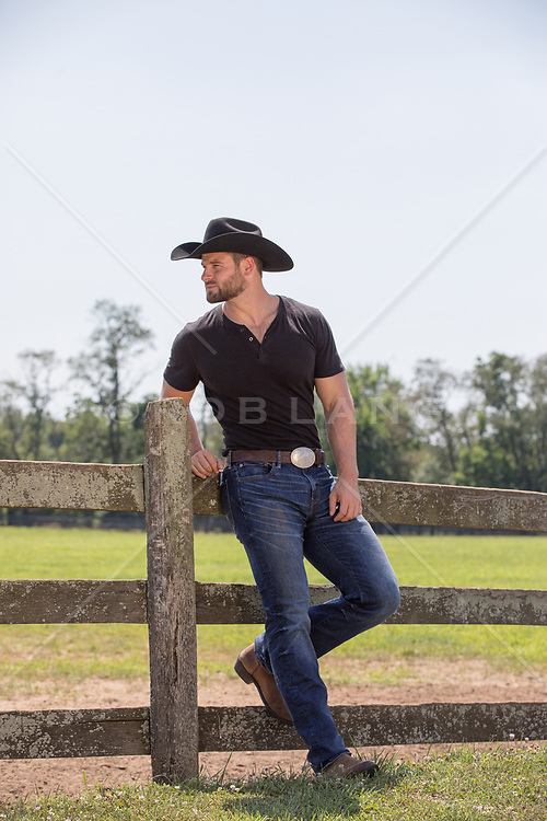 rugged cowboy by a spilt rail fence on a ranch