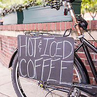 "Sign for ""hot and iced coffee"" at the Coffee Pedlar, a mobile bicycle coffee cart that he often parks at Pritchard Park in downtown Asheville, North Carolina."