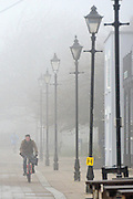 © Licensed to London News Pictures. 21/01/2014. Hammersmith, UK . A man cycles along the river front. People cross Hammersmith Bridge in heavy fog in West London today 21st January 2014. Photo credit : Stephen Simpson/LNP