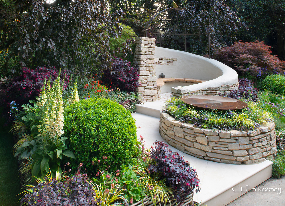 A circular stone seating around surrounded by plants in the Miles Stone: the Kingstone Maurward garden at the RHS Chelsea Flower Show 2019, London, UK