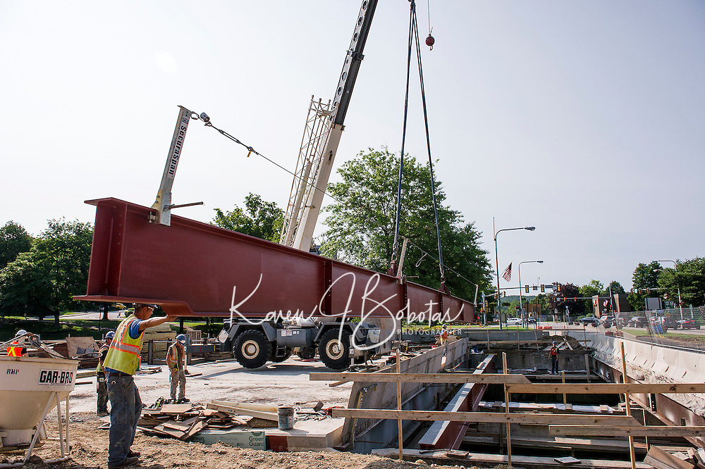 The second of two steel girders measuring 75 ft in length and weighing approximately 11,000 pounds swings around to be lowered and set into the Main Street portion of the Winnipesaukee River Bridge Friday morning.  (Karen Bobotas/for the Laconia Daily Sun)