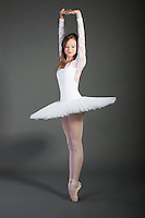 Young female ballet dancer posing over grey background